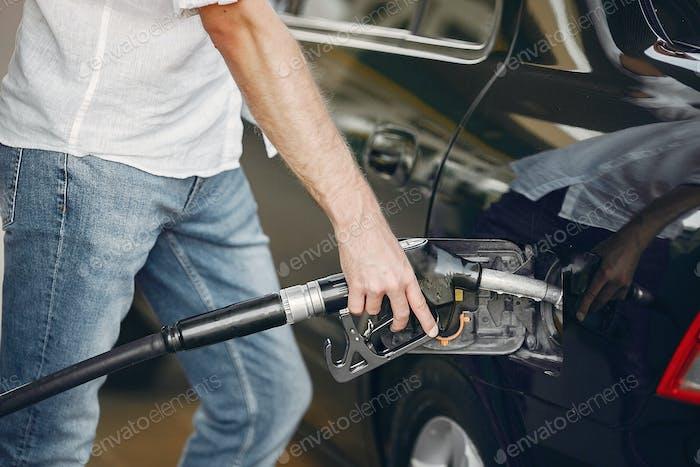Schöner Mann gießt Benzin in den Tank des Autos