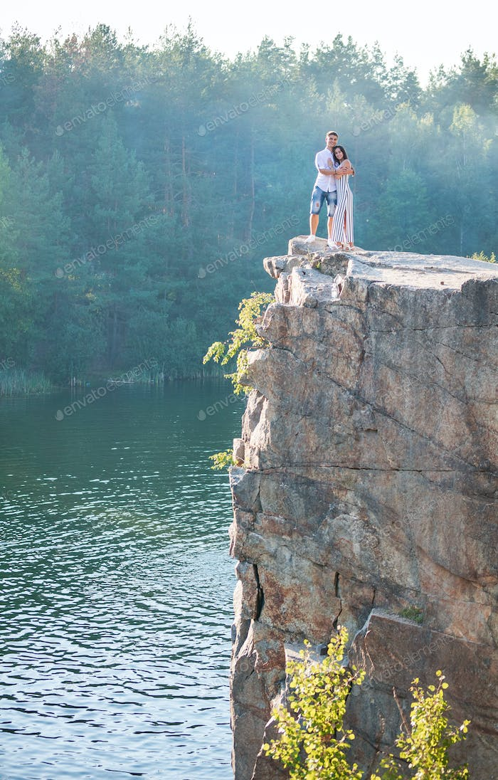 Romantic couple standing on cliff over river
