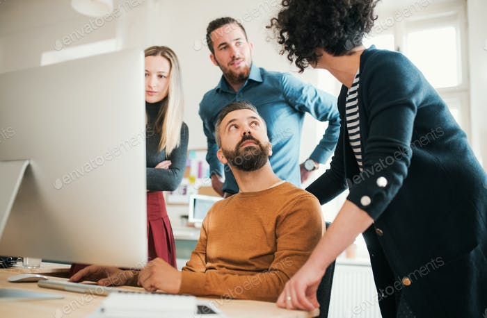 Group of young businesspeople with laptop having meeting in a modern office.