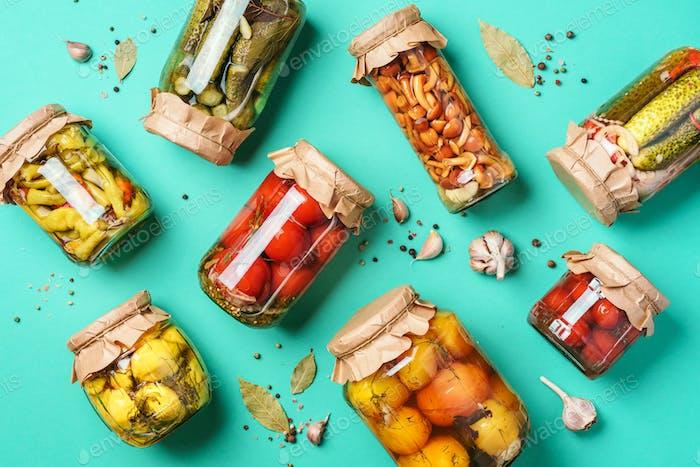 Konserviertes und konserviertes Gemüse in Gläsern über blauem Hintergrund. Draufsicht. Flache Lag. Kopierbereich