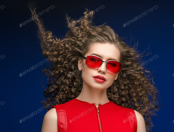 Attractive woman in red sunglasses emotional portrait fashion female with long  curly hair