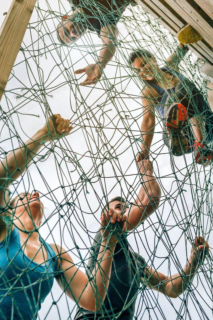 Participantes en la red de escalada del curso de obstáculos