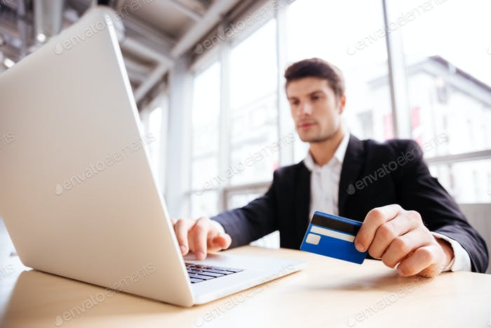 Businessman using laptop and credit card in office