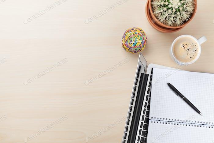Письменный стол с ноутбуком, кофе и кактусом