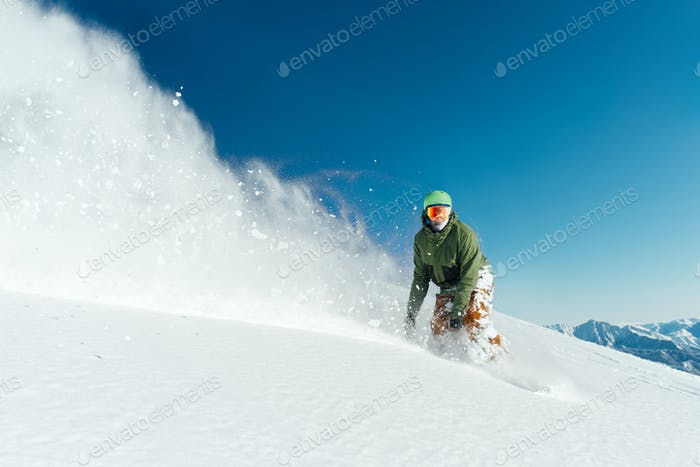 male snowboarder curved and brakes spraying loose deep snow on