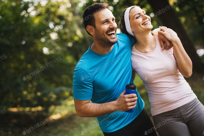 Exhausted fit couple runners after fitness running workout outdoors