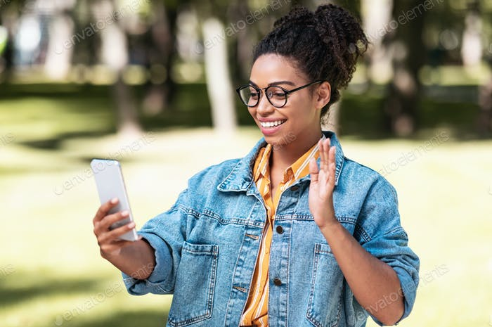 Black Young Woman Using Phone Making Video Call Walking Outside