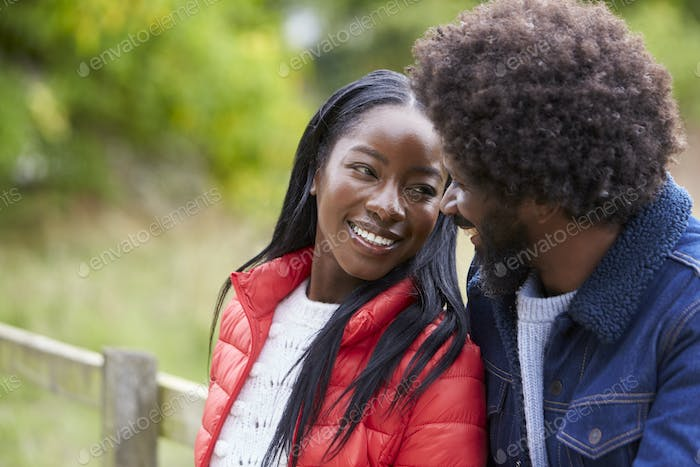 Happy black couple leaning on a fence in the countryside looking into each otherÕs eyes, close up