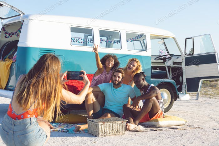 Young Caucasian woman taking pictures of her friends with mobile phone near camper van at beach