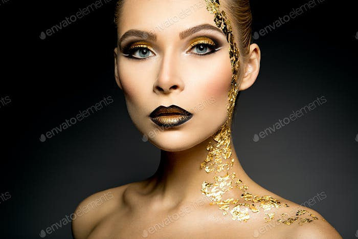 Beautyful girl with gold glitter on her face and body