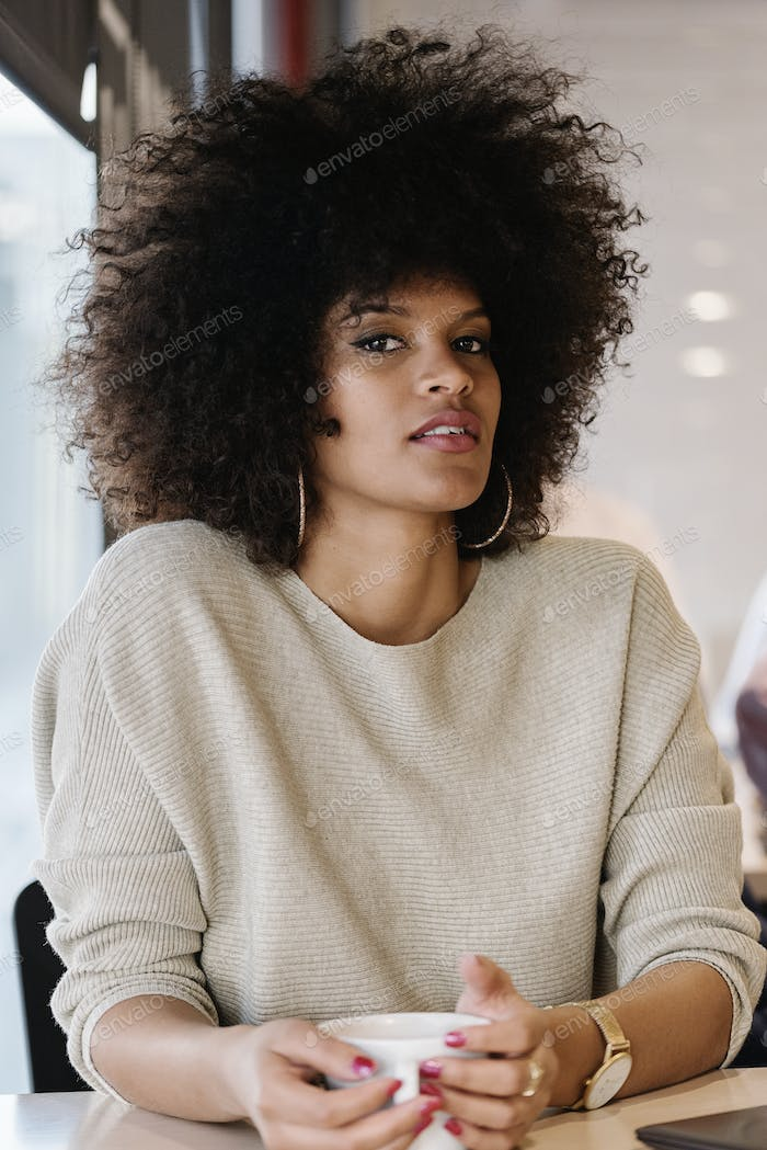 Portrait of attractive afro woman in coffee shop