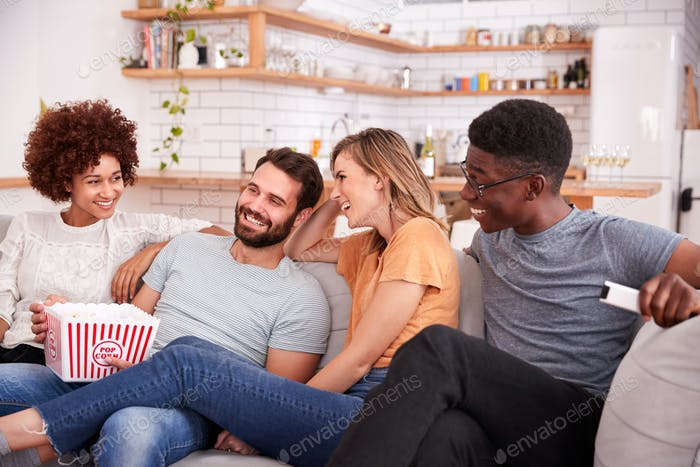 Group Of Friends Sitting On Sofa And Watching Movie At Home Whilst Eating Popcorn