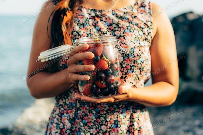Nahaufnahme eines Glases mit saftigen Beeren wird von einer Frau gehalten.