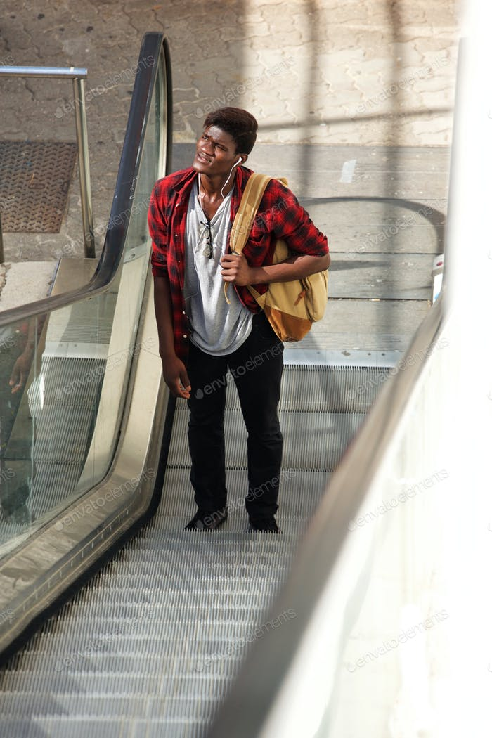 Young african man standing on escalator