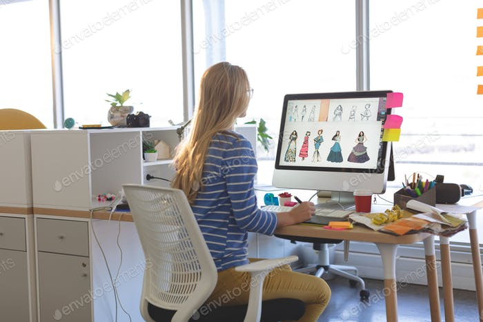 Young female fashion designer using graphic tablet while working at desk