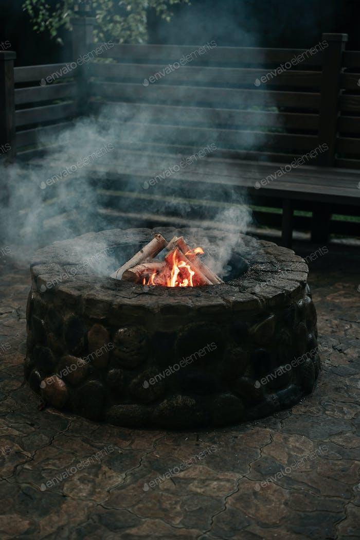 Flamme und Rauch von Feuer im Steinofen