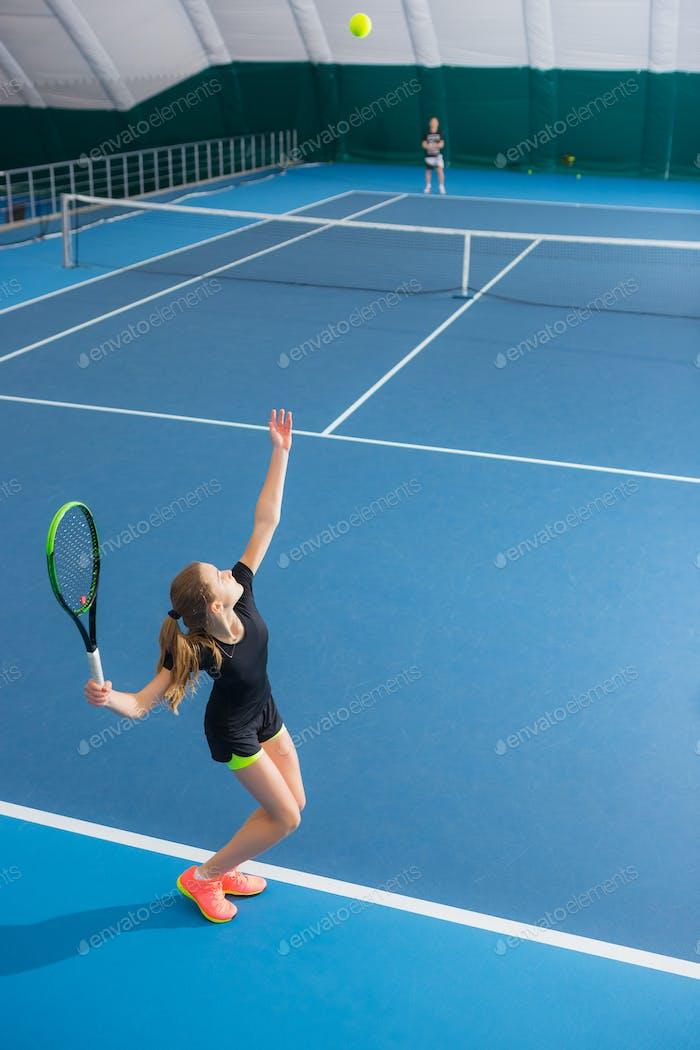 Das junge Mädchen in einem geschlossenen Tennisplatz mit dem Ball