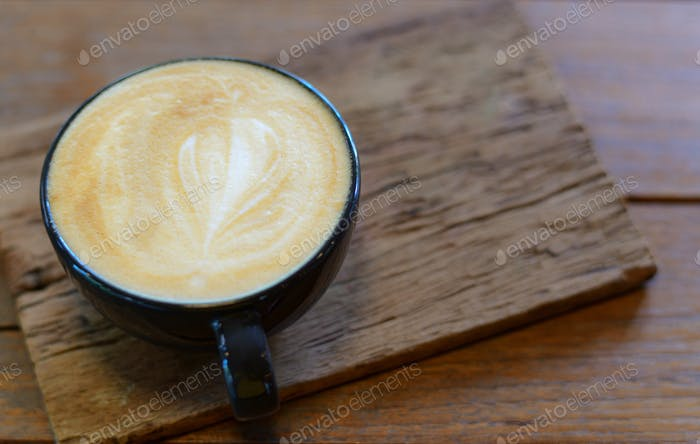 Latte coffee decorated with top leaves placed on wooden floor.