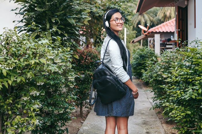 молодая стильная женщина ходит, слушает музыку на наушниках