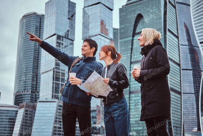 A handsome man showing the right direction and showplace to female tourists in front of skyscrapers