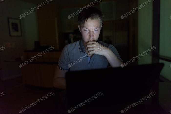 Young handsome man using laptop in the dark living room