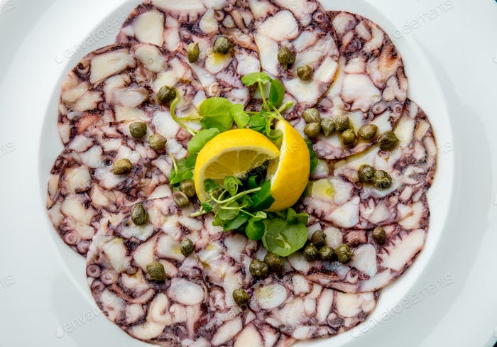 OCTOPUS CARPACCIO. Seafood Raw octopus slices with olive oil, lemon and capers on white plate. Top