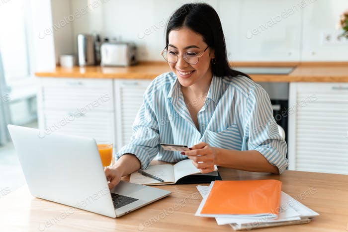 Woman using laptop computer holding credit card.