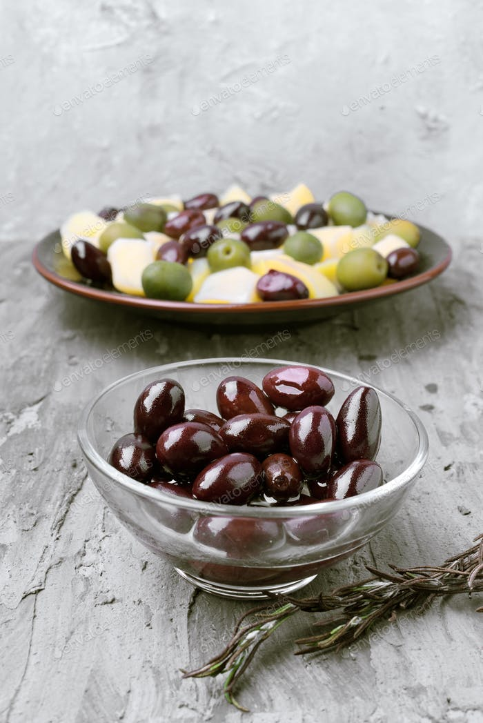 glass bowls with green and black olives, on gray rustic stage