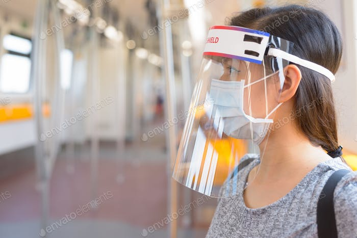 Young Asian woman wearing mask and face shield inside the train for protection from corona virus