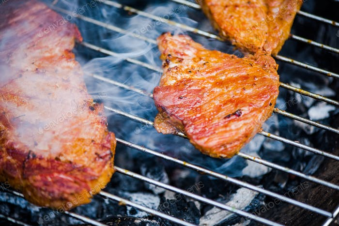 Close up view on meat on bbq hot grid grilling