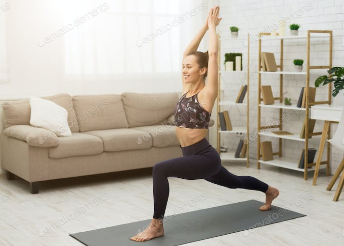Fitness concept. Happy woman practicing yoga at home