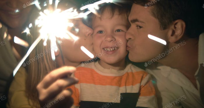 Parents, child and sparkler at night