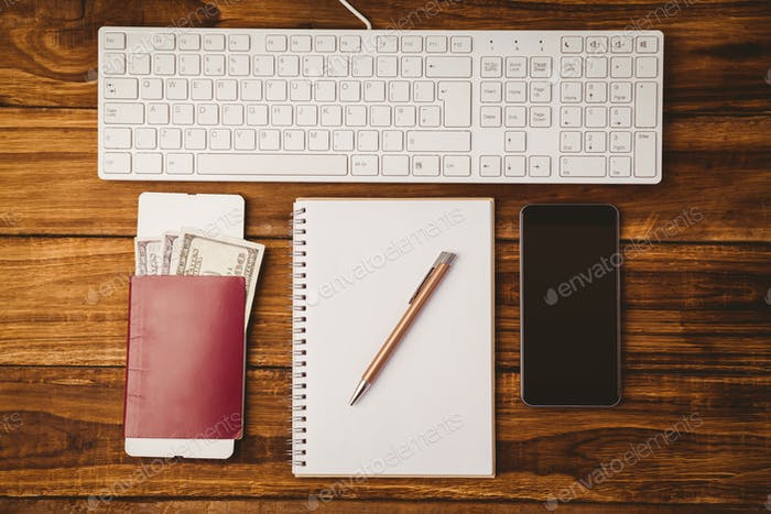 Pen on notepad passport smartphone and keyboard on wooden table