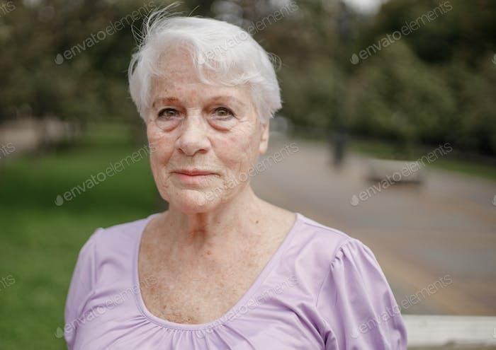 Fotoporträt einer alten Frau in einem Park an einem warmen Tag