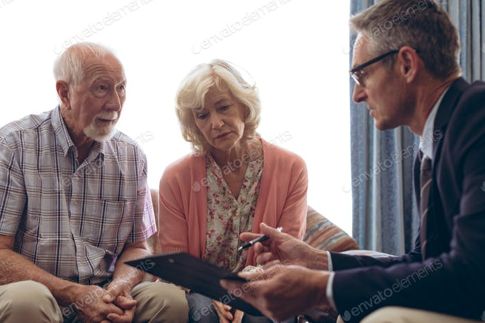 Male doctor interacting and showing papers to senior couple at retirement home