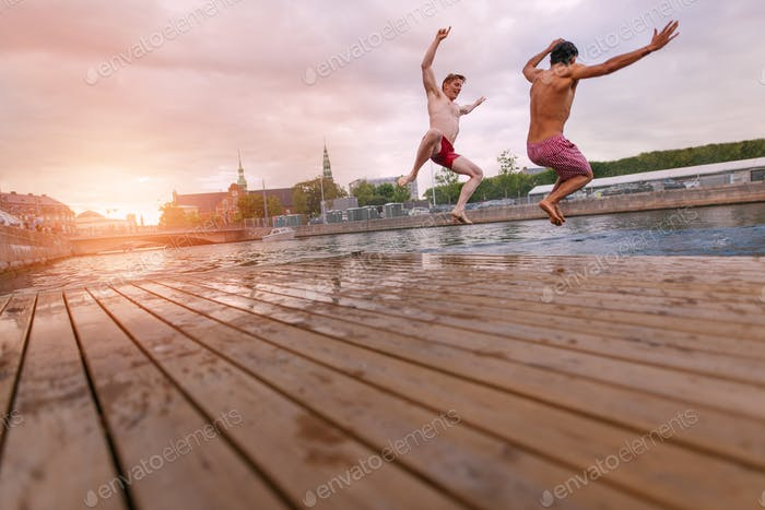 Young people jumping into lake in city