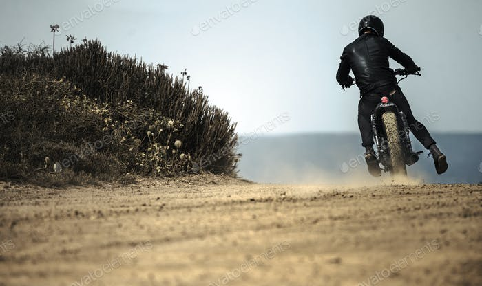 Rear view of man wearing crash helmet and black leathers riding cafe racer motorcycle on a dusty