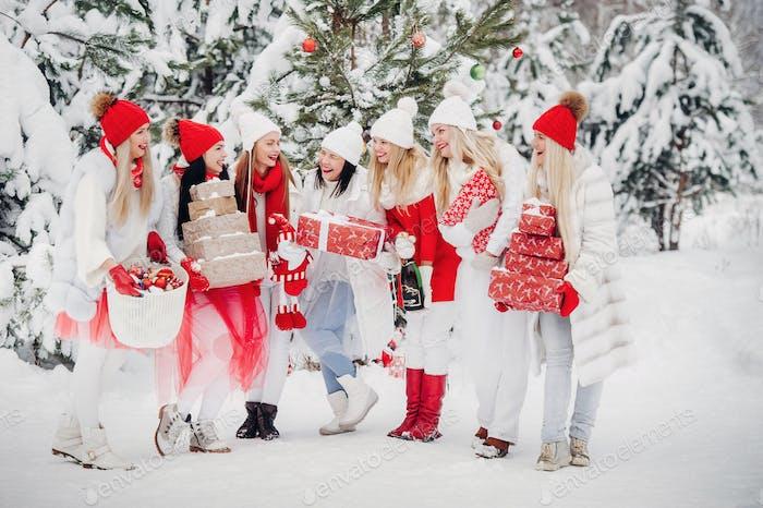Eine große Gruppe von Mädchen mit Weihnachtsgeschenken in ihren Händen stehen im Winterwald.Girls in
