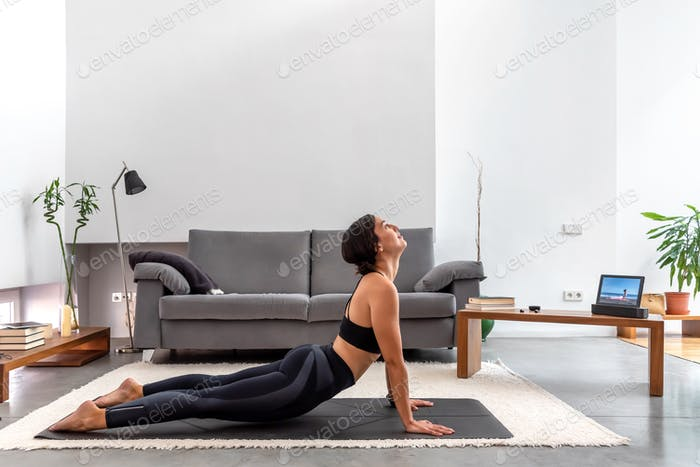 Fit woman practicing Cobra pose using online yoga training program in the tablet at home