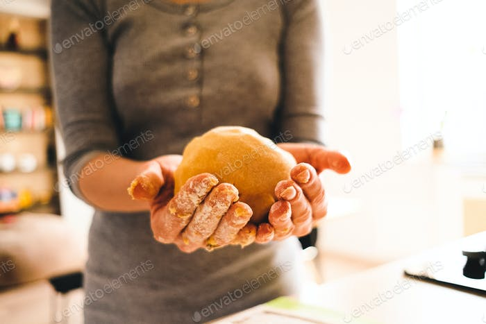 Woman holding dough with the ray of sun on her hands
