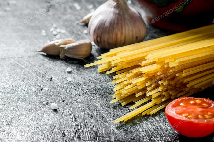 Raw spaghetti with garlic cloves and tomato.