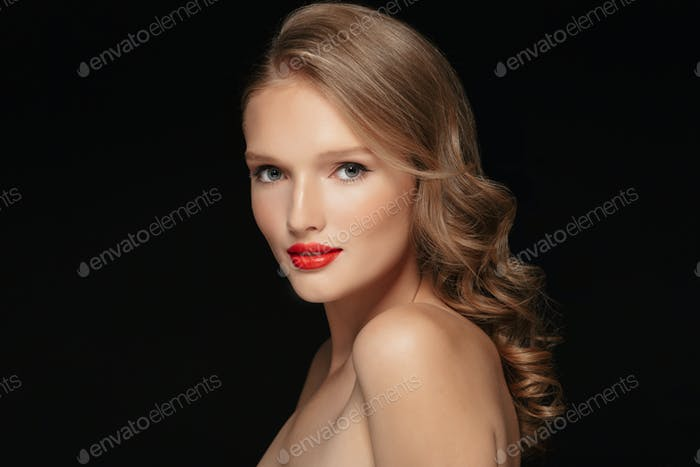 Portrait of young gorgeous woman with wavy hair and red lipstick
