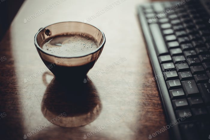 cup of coffee on  table near the keyboard