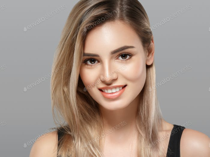 Beautiful young woman portrait smiling posing attractive blond gray background