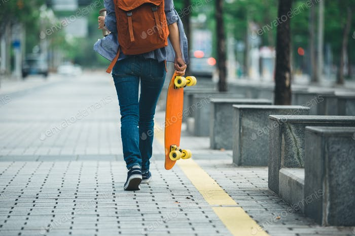 Woman with skateboard on city
