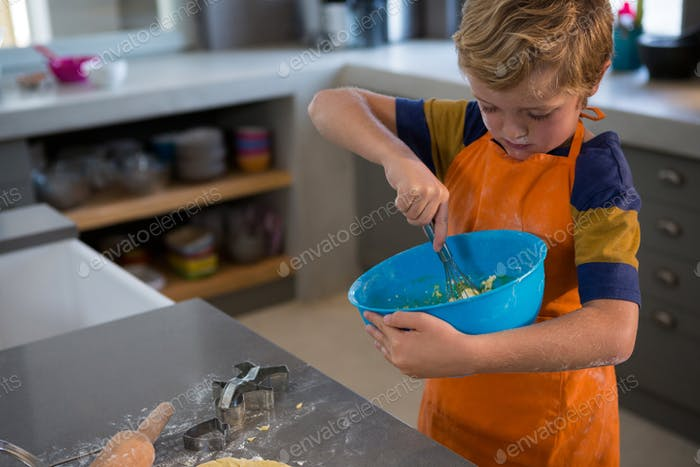 Boy mixing batter in bowl