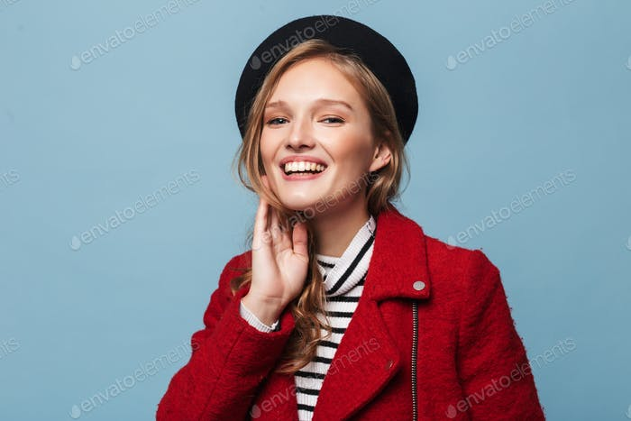 Young beautiful smiling woman with wavy hair in beret and red jacket joyfully looking in camera