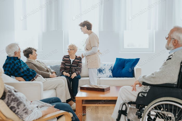 Head nurse is talking to new patients sitting on the sofa in a retirement home