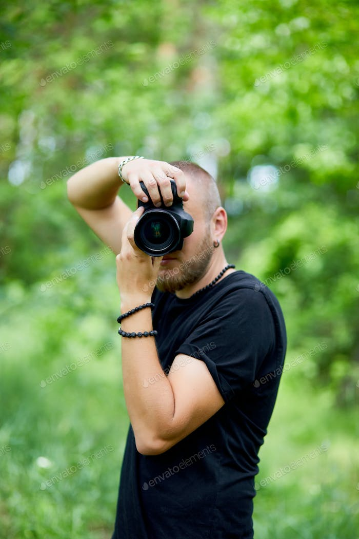 Portrait of a male photographer covering her face with the camera