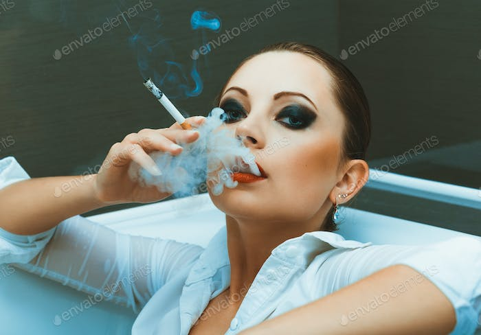 Young girl in a white shirt with bright makeup lying in the bath